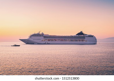 Luxury cruise ship sailing from port at sunset