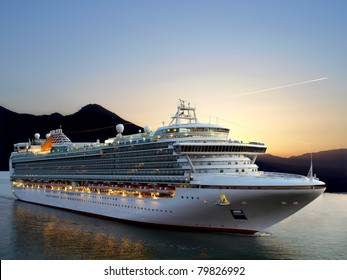 Luxury cruise ship sailing from port on sunrise.
