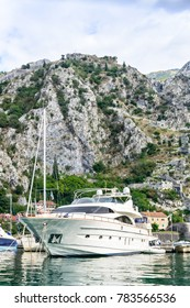 A luxury cruise yacht near the shore against the mountains and the blue sky, the port of Tivat