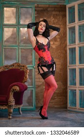 luxury dancer model posing in red corset with black lace, long gloves,  garters and nylon stockings with seam