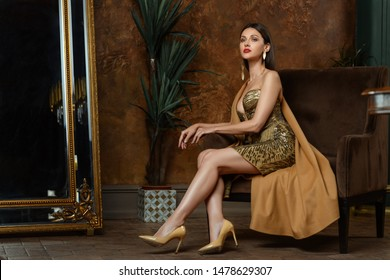 Luxury dark brown straight hair brunette female fashion green eyes model Olga Alberti gold earrings collar necklace chain neckline dress seat hands armchair shoes profile vintage interior tree flower
