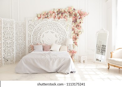 luxury delicate interior of the living room and bedroom in light colors with expensive chic carved furniture in classic style