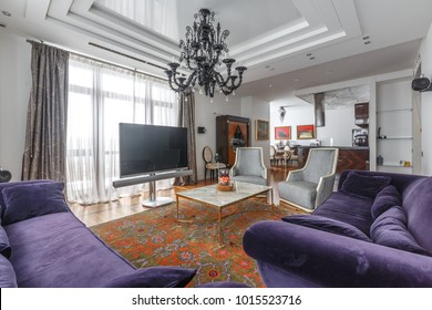 luxury designed living room with hardwood floor, natural vintage carpet, purple sofa, big tv and marble and steel table, panoramic windows and natural light