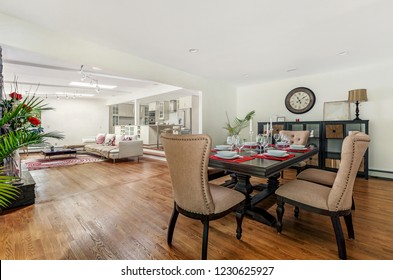 Luxury dining room with view on living room, white walls, wooden floor. Bright.