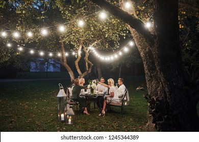 Luxury dinner. Evening time. Friends have a dinner in the gorgeous outdoor place.