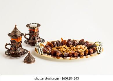 Luxuriöse Dry Date Früchte, Walnuss, Pistachio, Haselnüsse und Mandeln in der stilvollen, goldenen Schale mit Tee.Konzeptuelles Bild der islamischen Tradition Ramadan.