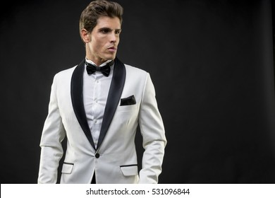 Luxury, elegant man in a white suit tuxedo with bow tie around his neck