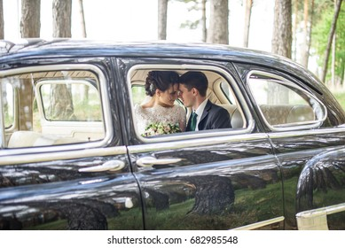 luxury elegant wedding couple kissing in stylish old black car . gorgeous bride and handsome groom in retro style. romantic moment
