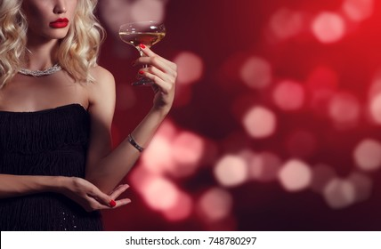 Luxury elegant woman with a glass of champagne on a background of holiday lights. The concept of the party.