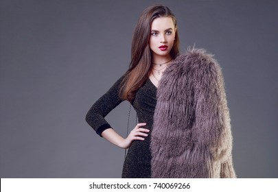 Luxury elegant woman with stylish  fur coat posing in studio , grey background.  Evening make up , red lips, brunette hairs.