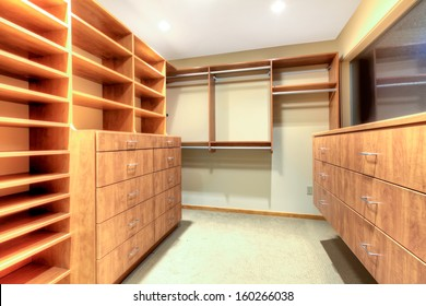 Luxury empty closet with wood build in shelves and cabinets.