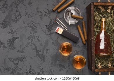 Luxury evening relaxation for men. Two portions of cognac, cigars and exclusive gift bottle on marble table, top view, copy space
