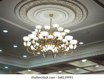 luxury expensive chandelier hanging under ceiling in palace.