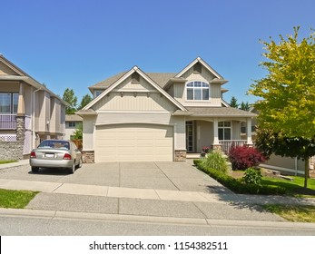 Luxury family house with a car parked on concrete driveway. Residential house on sunny day on blue sky background