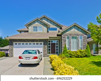 Luxury family house with luxury car parked on concrete driveway. Residential house on sunny day with blue sky background