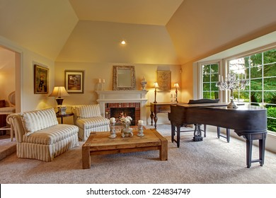 Luxury family room with high vaulted ceiling and large french window. Room has grand piano, fireplace, striped chairs and wooden coffee table