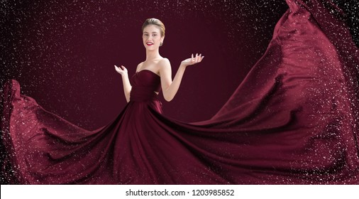luxury fashion of a beautiful woman  in flying silk dress. Glamorous woman wearing a red corset and Flying Fluttering Fabric skirt