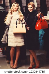 Luxury and fashion concept. Girls with smiling faces hold furry coats on clothes background. Friends in shop: ladies try expensive dark and white mink overcoats on. Women with purses buy furry coats.