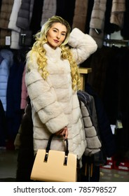 Luxury and fashion concept. Woman with blond hair buys furry coat. Girl with smiling face and purse wears furry coat on clothes rack background. Lady tries expensive white sable overcoat on.
