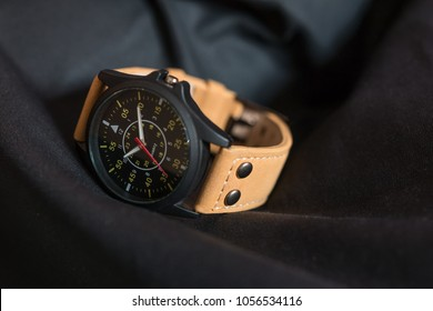 Luxury fashion watch with a black dial and brown leather in the vintage style for men on the dark background. Selective focus.
