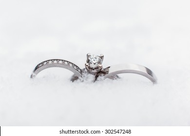 Luxury, fashion wedding three rings of gold, platinum, silver and precious stones, jewel of snow outdoors for the bride and groom on their wedding day. Wedding ceremony in the winter