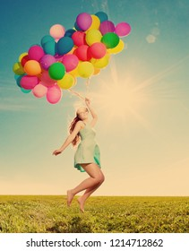 Luxury fashion woman with balloons in hand on the field against the sky and the sun in  long dress