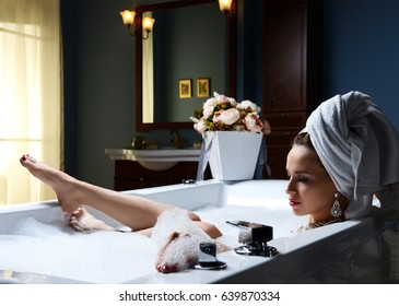 Luxury fashion woman with soft big towel in the evening in hotel spa lying in bath tub