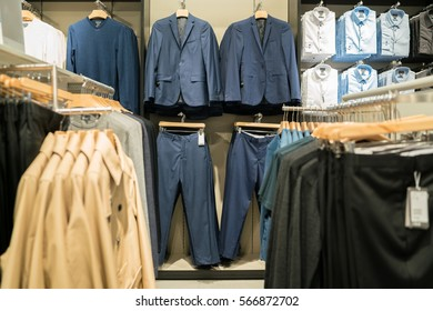 luxury and fashionable brand new for sale - interior of cloth store. shirts at shelf in shop shopping mall.