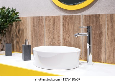 Luxury faucet mixer on a round bowl white sink in a beautiful beige wooden and yellow colour bathroom