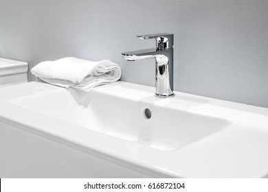 Luxury faucet mixer and white towel on a white sink in a beautiful gray bathroom