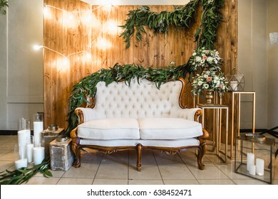 Luxury festive wedding decoration with flowers, vintage sofa and candles.