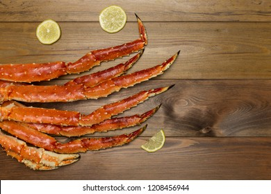 Luxury food. Crab claws with lemon slices on brown wooden background