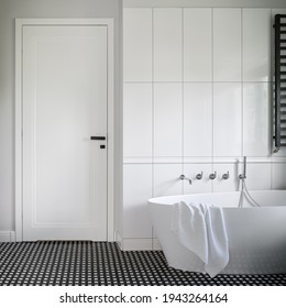 Luxury freestanding bathtub in black and white bathroom with stylish mosaic tile floor and white doors with black handle