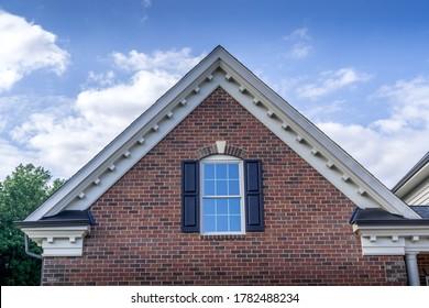 Luxury gable with sash window, dark shutters, on a brick siding, decorative beam end cornice on a new house cloudy blue sky
