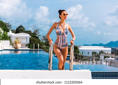 luxury girl model in the pool of an expensive hotel in a brand-new modern swimsuit. Apartments, private villa on a tropical island, an infinity pool, a trip, a vacation at sea