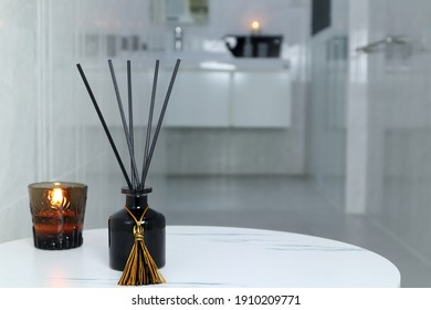 luxury glass aroma scent reed diffuser bottle and scented candle are used as air freshener in the nice white toilet bahtroom to creat relax , cozy and clean ambient