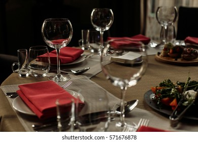 luxury glasses and plates with napkins on stylish decorated table at wedding reception. expensive catering at restaurant for celebrations. transparent glass and silver cutlery