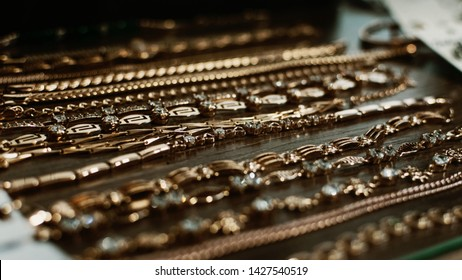 luxury gold jewelry chains, bracelets background, selective focus. Stylish beautiful bijouterie hanging on the stand in the accessories store. Various Jewelry bijouterie.