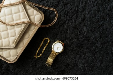 Luxury gold watch, beige leather bag and gold bracelet on black wool fabric texture background