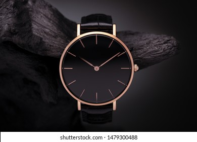 A luxury gold watch with a black dial. A watch on a beautiful stand, on a beautiful lightly lit gray background. Woman/Man fashion