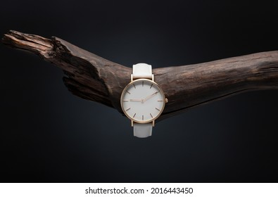 A luxury gold watch with a black dial. A watch on a beautiful stand, on a beautiful lightly lit gray background. Woman Man fashion. watch with white dial and white strap