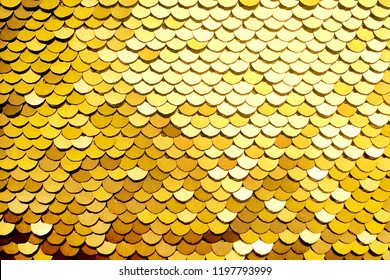 Luxury golden Background. Abstract Texture scales with gold Sequins close-up. Glamor Background with shiny Sequins on fabric, macro. Abstract background with gold sequins color on the fabric.