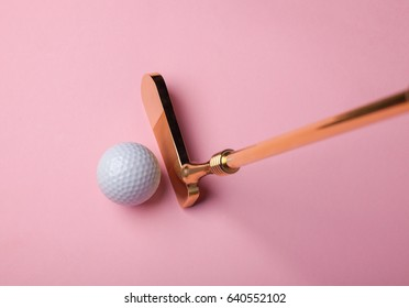 luxury golden golf club near golf ball on pink background