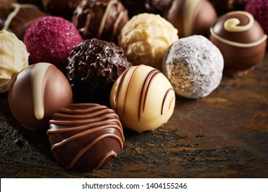 Luxury handmade decorative chocolate bonbon in a display of assorted pralines with selective focus in close up view on rustic wood