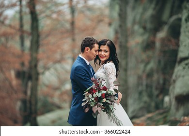 Luxury happy wedding couple kissing and embracing in forest with rocks