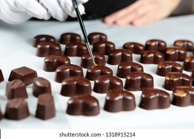 Luxury heart painted with gold on white background. Exclusive handmade chocolate candy. Product concept for chocolatier - Image