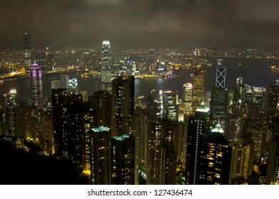 Luxury hilltop looking out over the dramatic night time neon lights and illuminated skyscrapers, crowded high-rise apartment blocks and futuristic architecture of Hong Kong Island from Victoria Peak