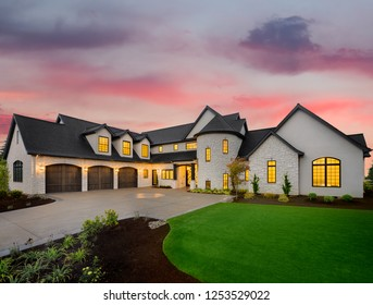luxury home exterior: mansion with green yard and three car garage with glowing interior lights and sunset sky