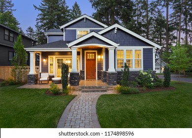 Luxury Home Exterior at Night: Beautiful New House with Green Grass and Landscaping at Twilight.Has Covered Porch and Glowing Interior Lights.