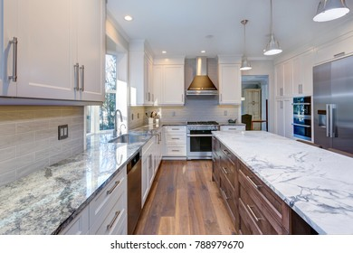 Luxury home interior boasts amazing white kitchen with custom white shaker cabinets, endless marble topped island and stainless steel appliances over wide planked hardwood floor.